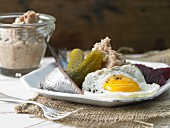 Labskaus (a traditional dish from Northern Germany) with soused herrings, fried egg and beetroot