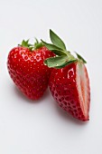 A whole strawberry and half a strawberry on a white surface