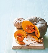 Two sliced pumpkins on a chopping board