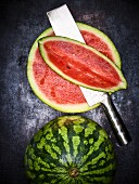 A whole and a sliced watermelon (seen from above)