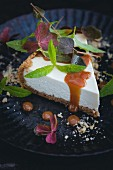 A slice of cheesecake with caramel sauce, lemon verbena and clover
