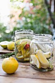 Pickled lemons in two jars on a wooden table