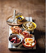 Tapas wth marinated artichokes, grilled chilli peppers, olives, eggs and a ham & tomato baguette