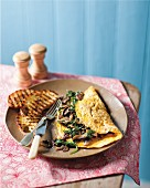 An omelette with mushrooms, baby leaf spinach and truffle oil