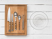 Kitchen utensils: knives, cutlery, a whisk and glass bowls