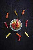 Colourful fusilli in a glass and scattered next to the glass