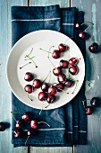 Fresh cherries on a plate and next to it