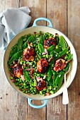 Chicken thights with shallots, broad beans, peas, mangetout and raisins