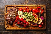 Grilled Black Angus Steak Striploin and vegetables on cutting board
