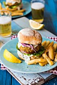 A fish burger with chips and beer