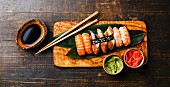 Nigiri Sushi Set on bamboo green leaf on olive wood board with soy sauce on wooden background