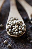 White peppercorns on a wooden spoon (close-up)