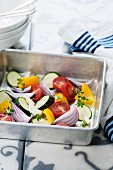 Fresh vegetables in a roasting tin (courgette, onion, tomatoes, yellow pepper, garlic and thyme)