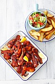 Barbecued chicken drumsticks and wings with potato wedges and salad