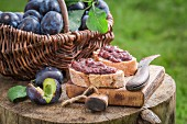 Bread topped with plum jar on a wooden board in the garden