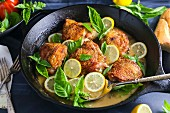 Chicken with lemon and basil in a pan