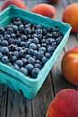 Blueberries in a cardboard punnet surrounded by peaches