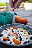 A hand sprinkling blueberries onto yoghurt with berries and peach slices