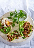 Ginger and chilli pork in lettuce cups topped with a soft-yolk poached egg