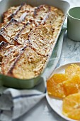 Baked French toast with slivered almonds and orange slices