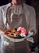 A woman holding a fruit pie with a lattice top and rose flowers