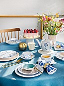 A tea table set in East Friesian style in blue and white with a bouquet of flowers