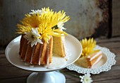 A yellow cake with flowers, one slice removed