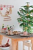 Weihnachtstisch mit Hyazinthen in nostalgischen Tassen, Stollen und Espressokanne, im Hintergrund Tannenbäumchen mit Strohdeko und Girlande aus getrockneten Apfelscheiben an der Wand