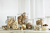 Various types of nut in glass jars on a rustic kitchen table