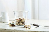 Brazil nuts in and next to a glass jar on a rustic kitchen table