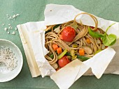 Spaghetti en papillotte with vegetables and basil oil