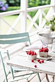 Raspberries in a small bowl on a terrace table