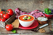 Hot tomato puree soup with beans, decorated with sour cream and basil