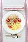 Rabbit with cherry tomatoes and ribbon noodles (top view)