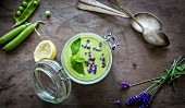 Green gazpacho in jar with peas and lavender on wooden background with vintage spoons