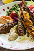 Moroccan kebabs with hummus and lettuce
