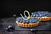 Two Lemon tartlets with fresh blueberries, served on black stone slate with lemon and lemon zest over black background