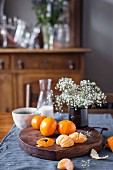 Clementines and flowers on a rustic wooden board