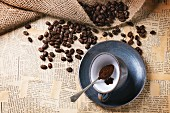 Blue ceramic cup with ground coffee and roasted coffe beans over old newspaper