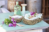 White porcelain bowls with wooden cutlery in hay baskets and horned violets on a vintage kitchen table