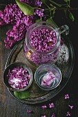 Arrangement with vintage iron bowl of lilac flowers in sugar, jug of lilac water, ice cubes in glassand lilac branch