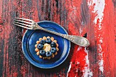 Top view on blueberry mini tart served on blue ceramic plate with vintage fork over black and red wooden background