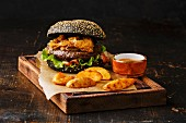 Black burger with sesame seed bun, meat, bacon, onion fries rings and potato wedges on dark wooden background