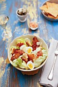 A lettuce salad with boiled eggs, bacon and spicy croutons
