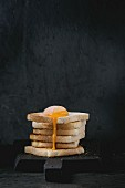 Pile of toasts bread with flowing sugared yolk on black wooden cutting board over black textured background
