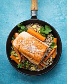 Fillet of salmon on a bed of buckwheat with carrots, coriander, broccoli and yellow pepper