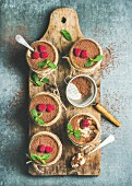 Tiramisu in glasses with mint leaves, fresh ripe raspberries and cocoa powder on rustic wooden board