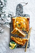 Fish pie on a chopping board in the snow at Christmas