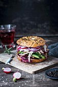 Spelt bagel with black sesame, radishes, green peppers, red onion and pulled chicken