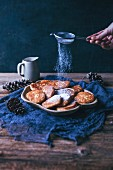 Woman s hand dusting sweet fritters with powdered sugar